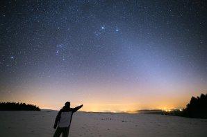 Slabé zvířetníkové světlo nad Sečskou přehradou v roce 2013. Kužel světla táhnousí ze od obzoru zcela zprava šikmo až k horní části snímku zasahuje do krásných hvězdokup Plejády a Hyády v souhvězdí Býka. Na obzoru, kam ukazuje pozorovatel, se rozkládá nevlídný žlutavý odstín světelného znečištění. Autor: Petr Horálek