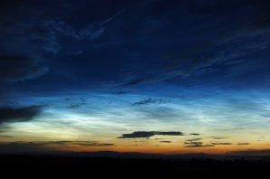 Jasné a rozsáhlé noční svítící oblaky ráno 12. července 2016 zachycené z Lučence. Byly pozorovatelné navzdory nasouvající se vysoké a střední oblačnosti, jejíž tmavé siluety jsou na snímku v popředí. Autor: Juraj Hanula