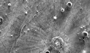 Infračervené snímky odhaľujú svetlé pruhy, ktoré sa tiahnu z krátera Santa Fe. Výskumy naznačujú, že pruhy boli spôsobené tornádom, ktoré vzniklo pri náraze meteoritov. Autor: NASA/JPL-Caltech/Arizona State University
