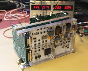 Napájecí zdroj (v popředí) pro misi ESA/JUICE v sestavě s palubním počítačem a vysokofrekvenčním analyzátorem radiového spektra v Institutu kosmické fyziky v Uppsale. Autor: AsÚ AV ČR.