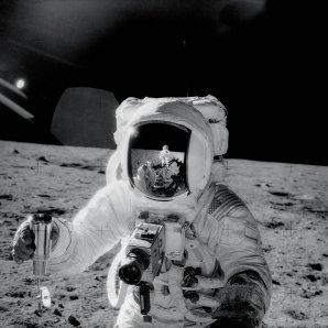 Alan Bean během práce na Měsíci, v pravé ruce drží zásobník se vzorkem lunární půdy. V jeho přilbě se odráží velitel Conrad. Autor: NASA
