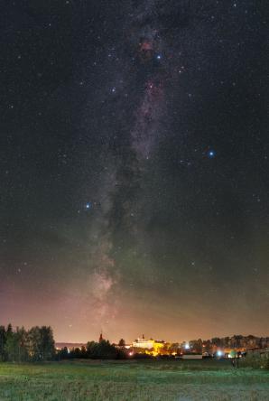 Mléčná dráha a airglow nad Broumovem, v dáli nad obzorem se tyčí Broumovský klášter. Autor: Petr Horálek.
