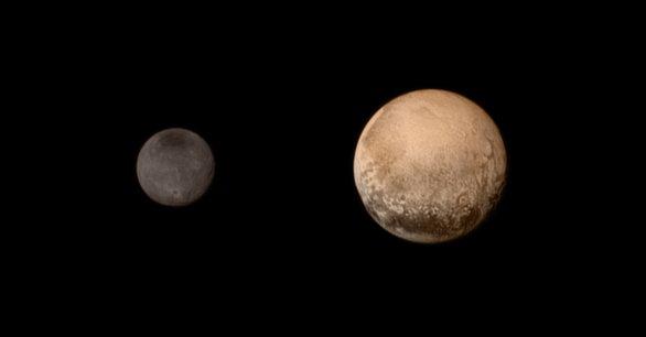 Pluto a Charon 13. července 2015 v barvách. Na levém okraji Pluta se zjevuje světlá plocha patrně pokryta zamrzlým metanem a dusíkem. Autor: New Horizons, NASA.
