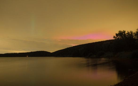 Ojedinělý záznam silné polární záře 23. června 2015 v řidší oblačnosti nad Sečskou přehradou. Na snímku je rudý nádech záře v díře mezi oblačností, ale rovněž zelený sloup, který byl tak jasný, že oblačností prosvítal. Autor: Petr Horálek