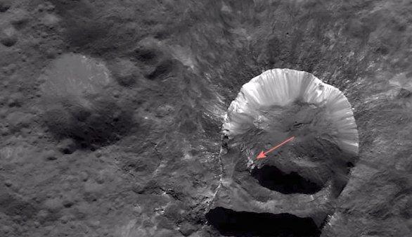 Šipka ukazuje světlou skvrnu v kráteru Oxo, která je zřejmě původcem detekce vody přímo na povrchu Ceresu Autor: NASA/Dawn