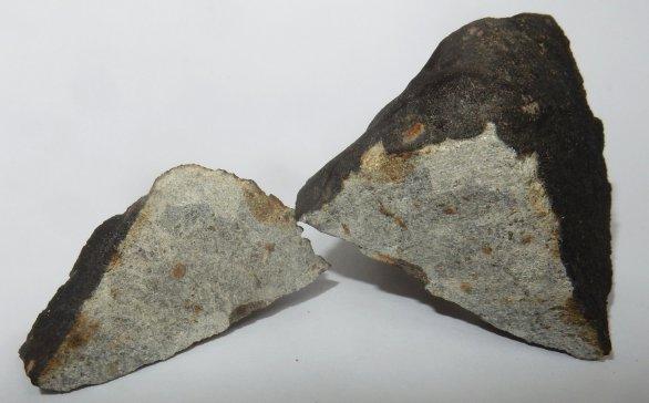 Meteorit Hradec Králové, který nalezl 30. 7. 2016 pan M. Maršík přesně ve vypočtené pádové oblasti. Na snímku je tento meteorit krátce po rozříznutí na dvě části – 22g (vlevo, deponován pro vědecké účely v Astronomickém ústavu AV ČR) a 109g (vpravo, vrácen nálezci). Meteorit byl klasifikován jako obyčejný chondrit typu LL5. Autor: Pavel Spurný, Astronomický ústav AV ČR.
