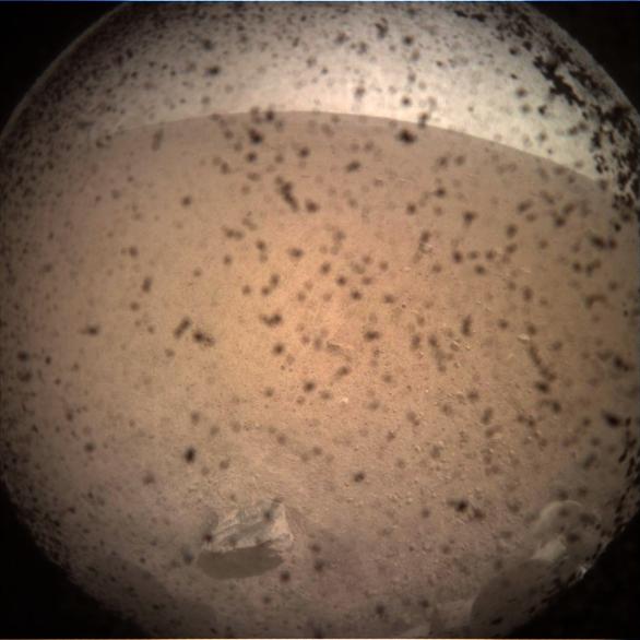 První snímek z povrchu, ještě s neodklopenou krytkou proti prachu Autor: NASA/JPL-Caltech