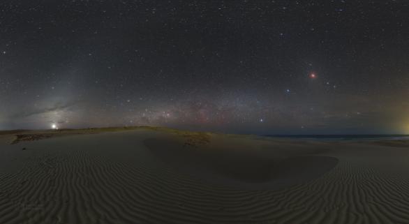 Zatměňová hodina 21. ledna 2019 nad dunami hluboko v Chaves, kde již neruší světelné znečištění. Vlevo vychází Venuše a Jupiter, vpravo leží na nebi zatmělý Měsíc poblíž hvězd Castor a Pollux. Nízko nad obzorem se rozkládá zapadající Mléčná dráha a přes oblohu se táhne slabý oblouk zvířetníkového světla. Autor: Petr Horálek.