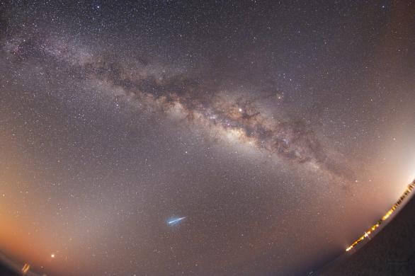 """Mléčná dráha z ostrůvku """"Sandbank"""", v pravém rohu je pak Soneva Fushi. Ve spodní části je 8minutový záznam zjasnění druhého stupně Falcon Heavy při zážehové sekvenci 12. dubna 2019. Autor: P. Horálek, L.L. Christensen / Soneva Fushi."""