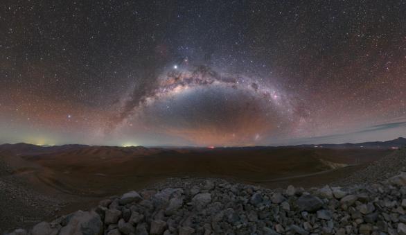 Oblouk Mléčné dráhy a výrazné červené airglow ve směru na východ od Cerro Armazones. Kameny v dolní části snímku vznikly po odstřelení vrcholu v roce 2014. V krajině pouště také uvidíte stín samotné hory (na úrovni pod centrem Mléčné dráhy), neboť v době focení ještě do zad slabě svítil Měsíc. Autor: Petr Horálek/ESO.