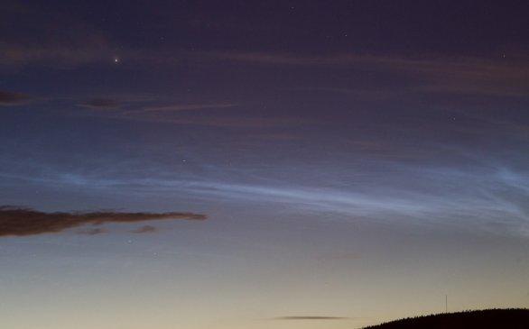 NLC, noční svítící oblaka, stříbromodrá struktura na pozadí blízkých tmavých oblak středních až vysokých pater. Fotografováno krátce po 23. hodině 6. června 2020. Jasná hvězda je Capella. Autor: Martin Gembec