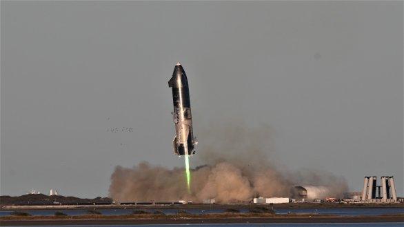 Starship SN8 těsně před dosednutím. Po úspěšném testu vidíme, že motory ztratily tah a pravděpodobnou absenci dostatku paliva naznačuje zelená barva plamene (kdy možná přebytek kyslíku ve spalovací komoře tavil měď v motoru). Autor: BocaChicaGal/NASASpaceflight.com