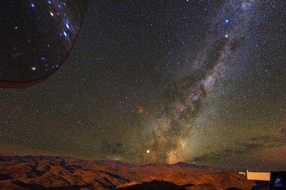 Mléčná dráha nad pouští Atacama ozářená zapadajícím Měsícem. Vlevo nahoře část parabolické antény radioteleskopu SEST. ESO, La Silla, Chile Autor: Zdeněk Bardon
