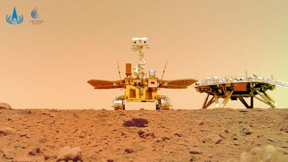 Snímek vozítka Ču-žung (Zhurong) vyfotografovaný z kamerky zanechané na povrchu Marsu. Vpravo i přistávací plošina mise Tianwen-1 Autor: CNSA