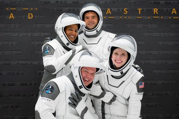"""Posádka soukromé mise SpaceX s názvem Inspiration4 (v pozadí morseovkou nápis """"ad astra"""" - """"ke hvězdám"""""""